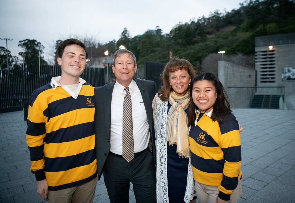Photo of two guests smiling at the camera, flanked by a pair of students in Rally Committee rugby shorts