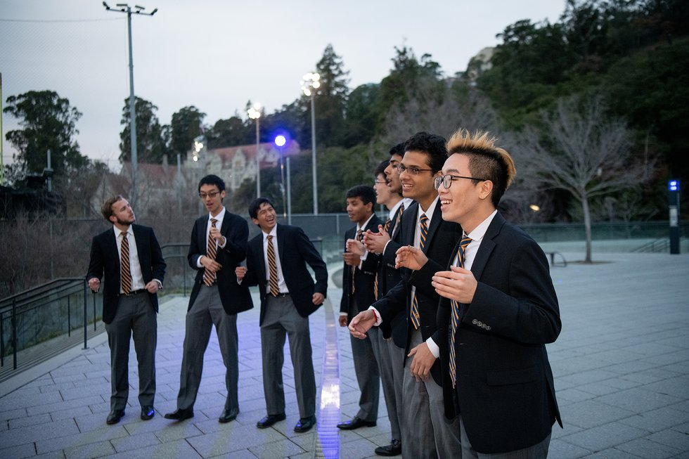 Photo of an a cappella singing group performing at the top of the steps to Memorial Stadium
