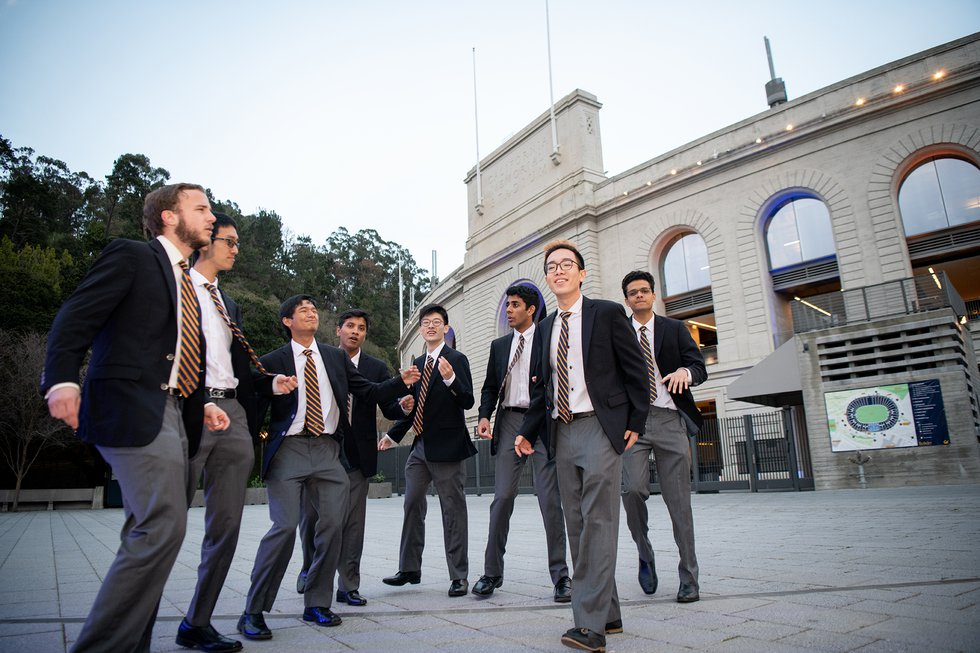 Photo of an a cappella singing group performing with Memorial Stadium in the background