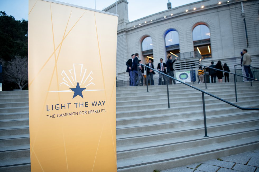 "Photo of a large, gold banner featuring the ""Light the Way"" campaign logo in blue, at the bottom of steps to the stadium"