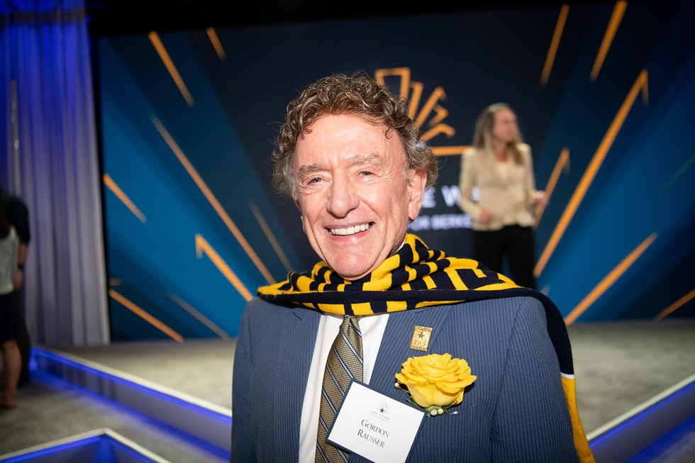 Photo of Gordon Rausser smiling, wearing a blue and gold scarf over a suit and tie