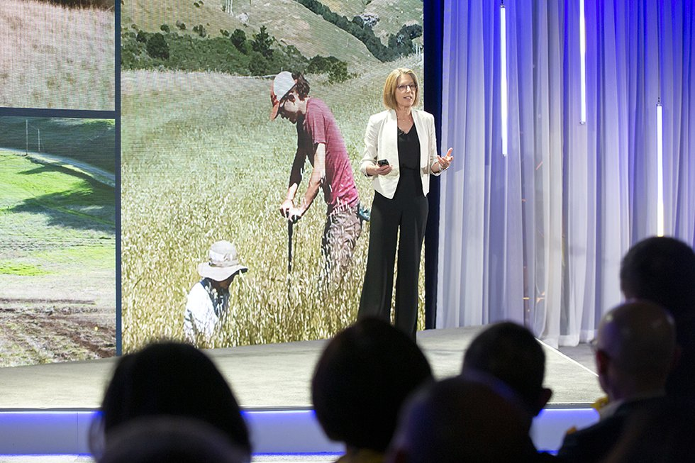 Photo of speaker onstage with photo of people working in a green field onscreen behind her