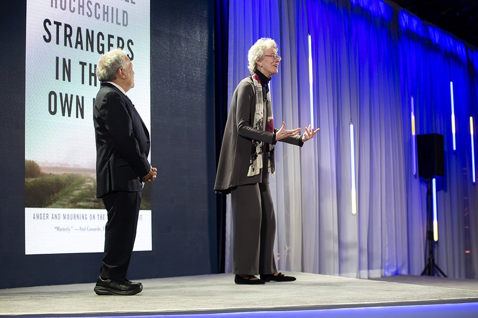 "Photo of Robert Reich and Arlie Hochschild onstage with her book ""Strangers in Their Own Land"" onscreen in the background"