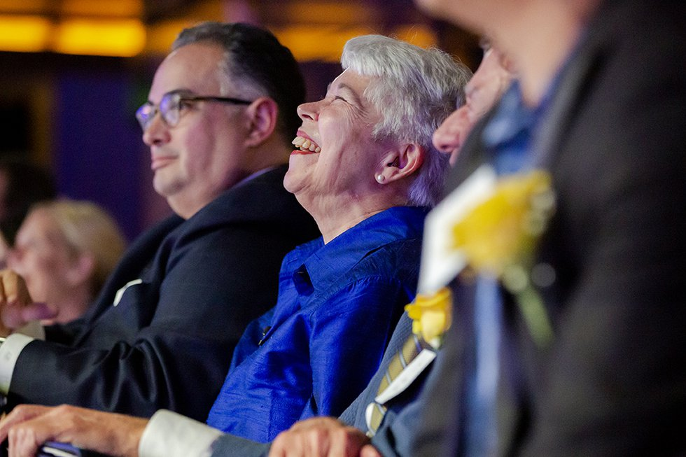 Photo of Chancellor Christ sitting in the audience, her head thrown back in laughter