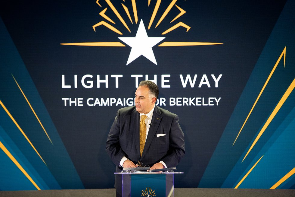 "Photo of presenter onstage with the ""Light the Way"" logo behind him onscreen"