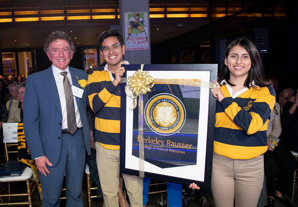 "Photo of Gordon Rausser standing next to two Rally Committee members holding a framed pennant reading ""Berkeley Rausser College of Natural Resources"""