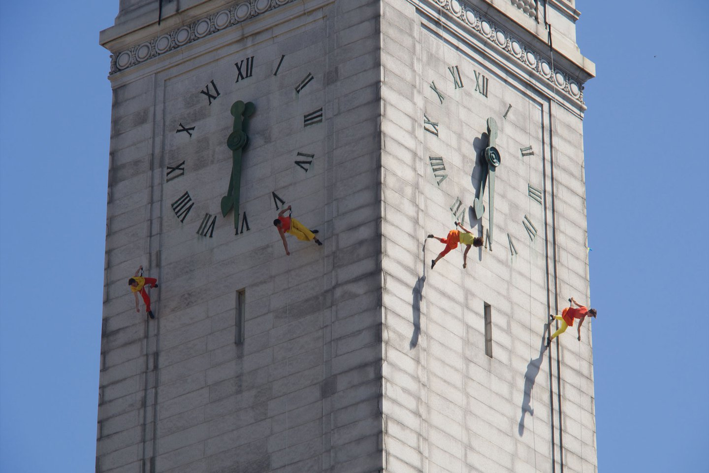 Photo of dancers in red tops and yellow pants hanging off the top of the Campanile.