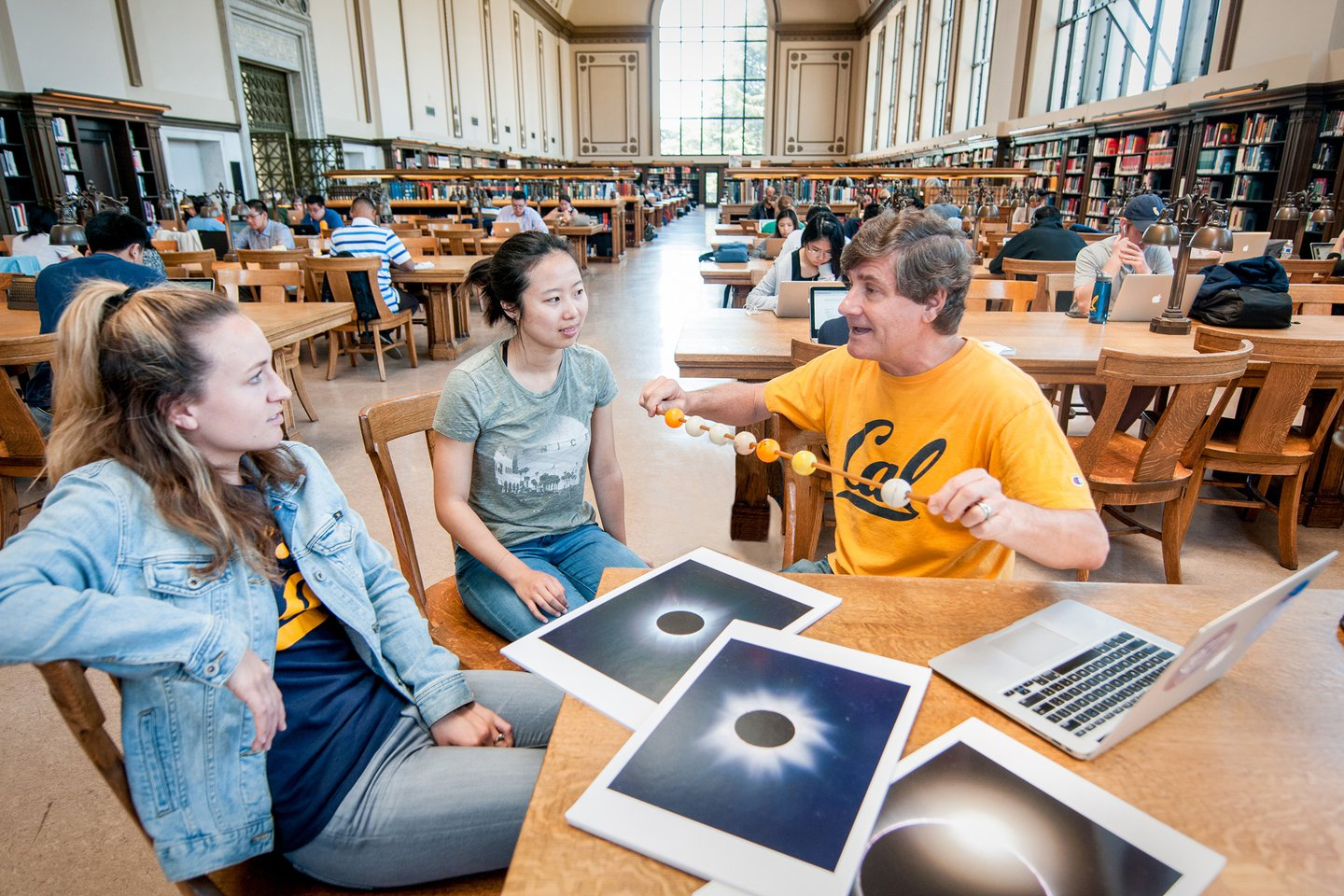 Photo of Alex Filippenko in a well-lit part of Doe Library, showing a simple model of the universe to two students