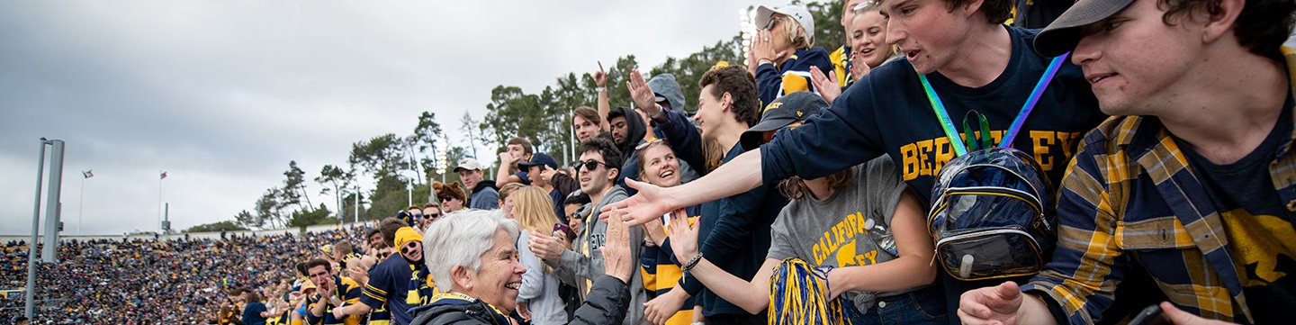 Photo of Chancellor Christ giving students in the stands at a ball game a high five.