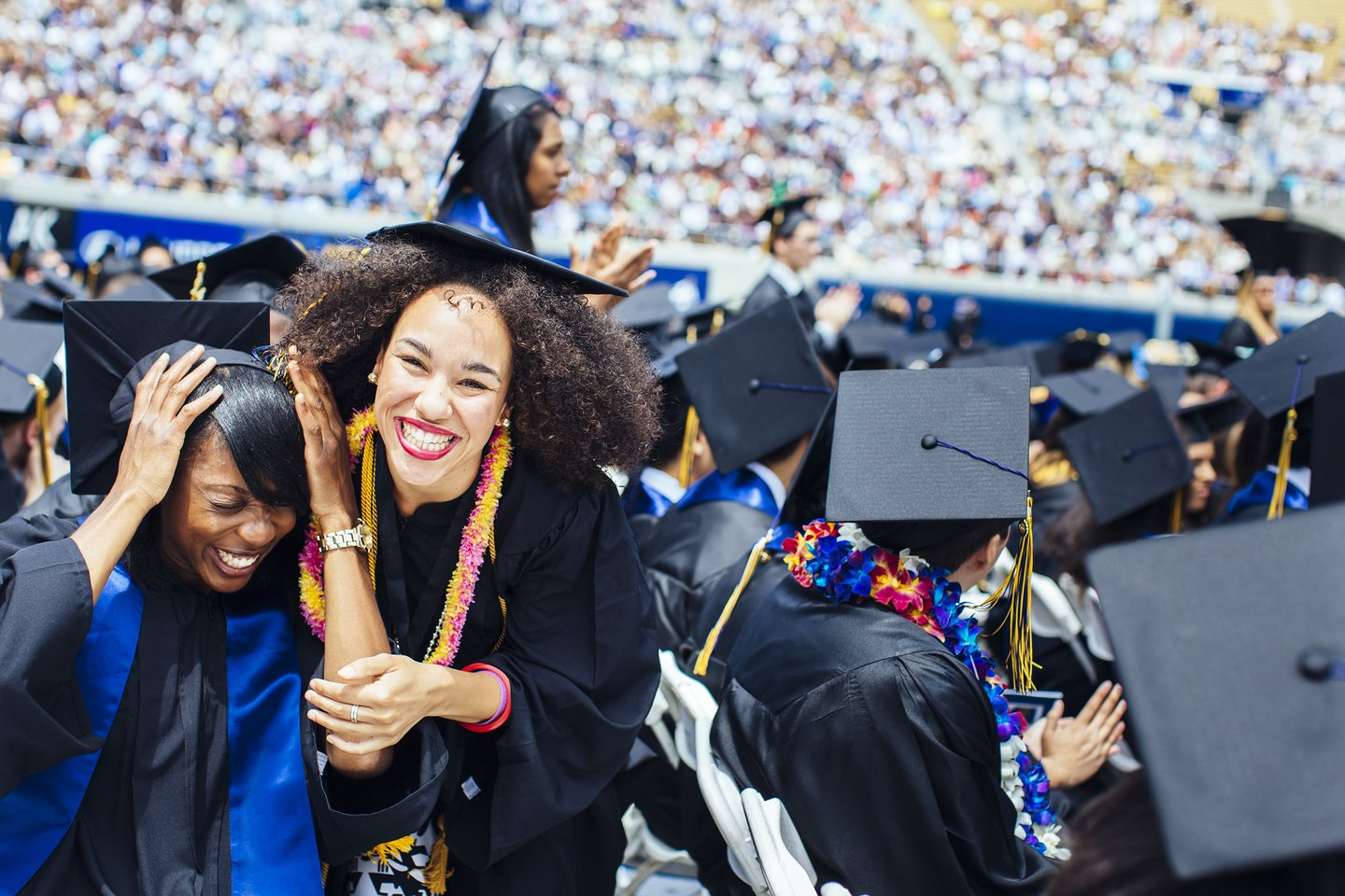 Photo of a sea full of graduating students in Memorial Stadium, two students smiling in foreground, one looks at camera