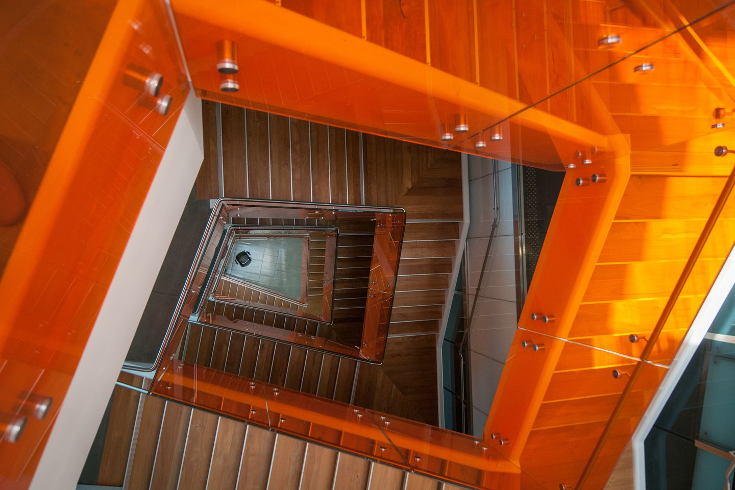Photo of a golden-brown wooden spiral staircase, looking down to a single chair at the bottom