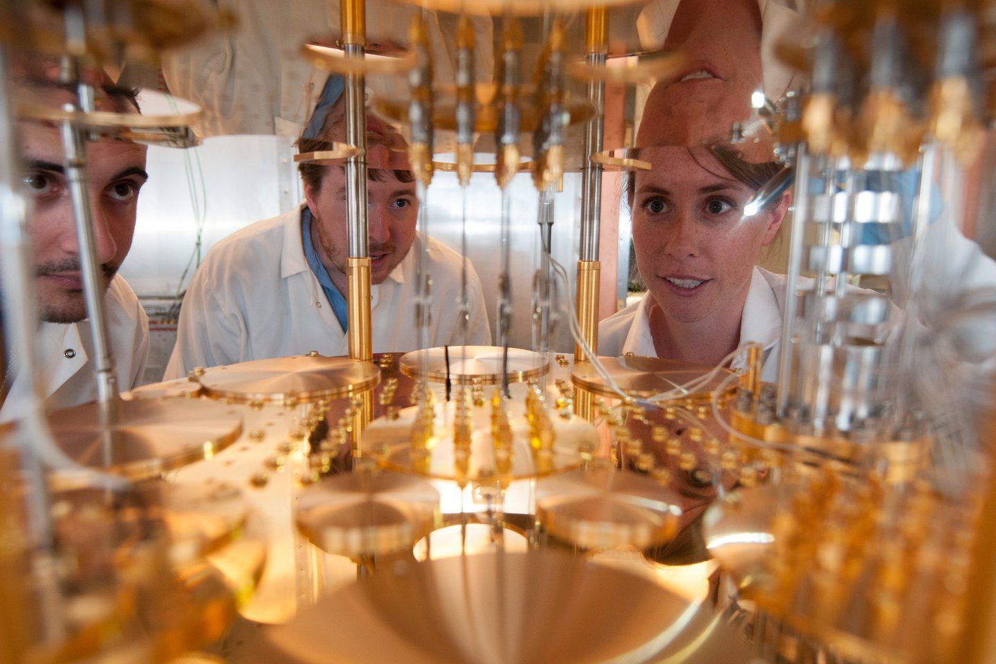 Photo of three students looking with wonder into a reflective, gold machine