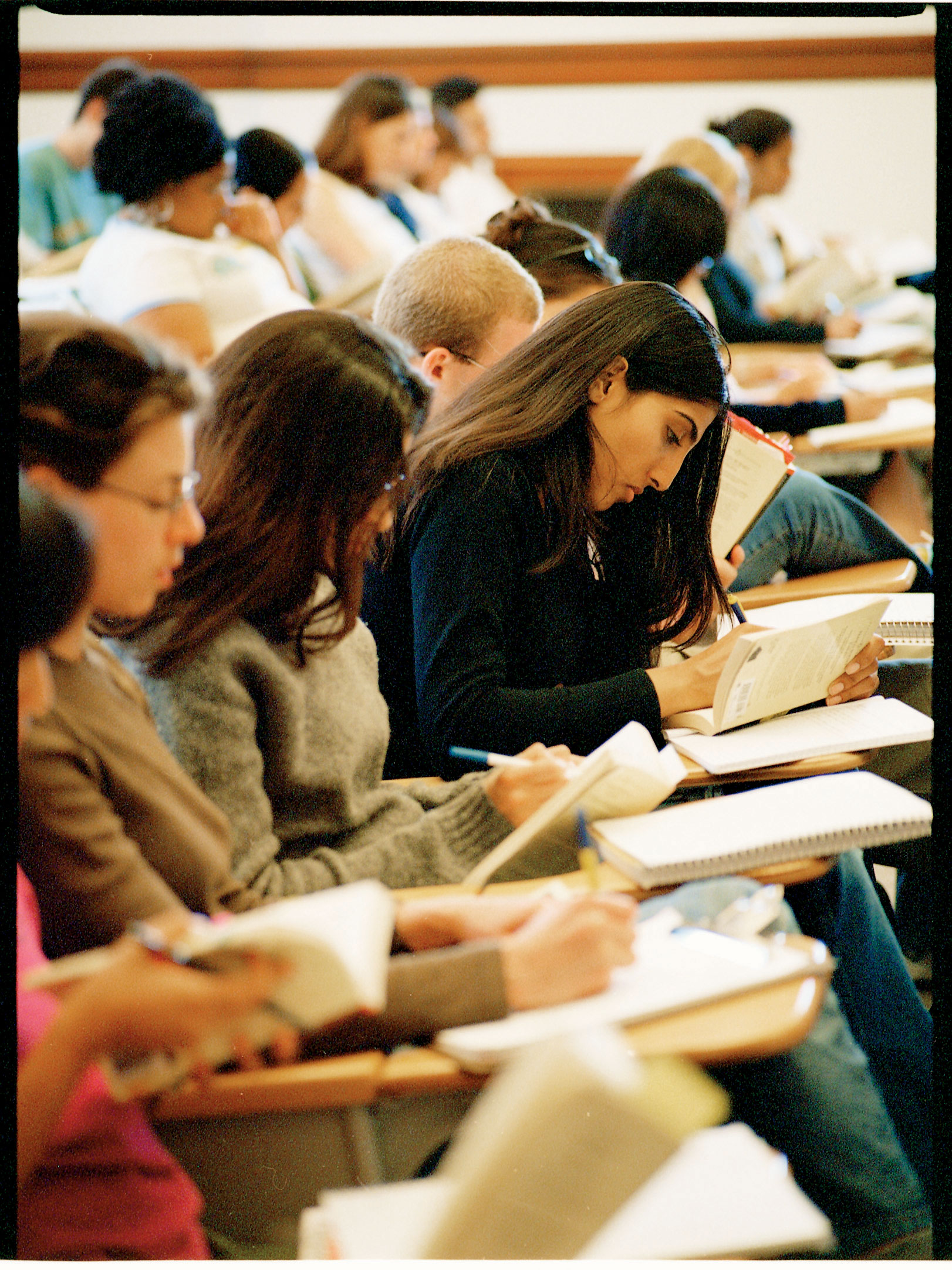 Close-up of a row of students highlighting pages in books, one woman's face particularly visible in profile
