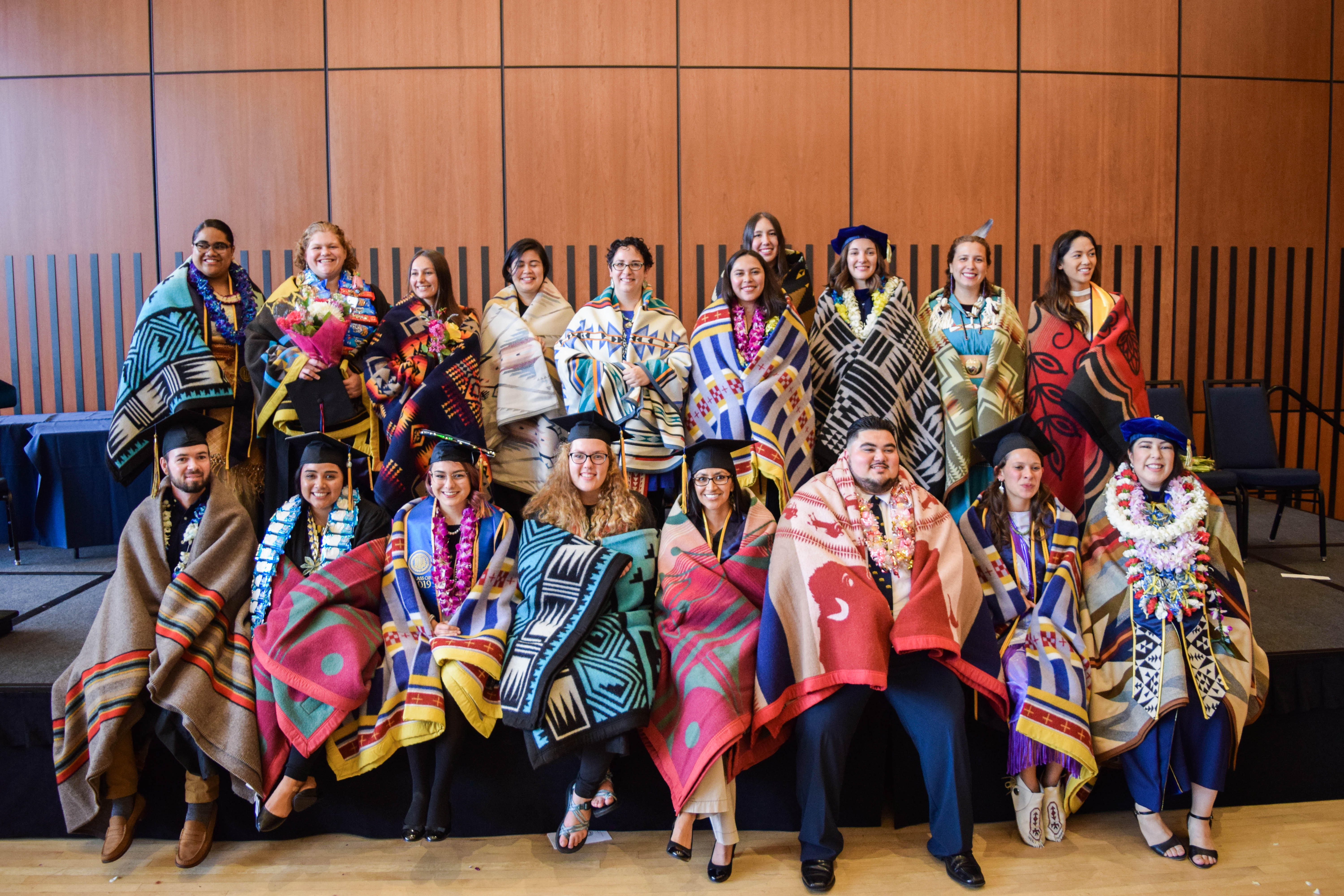 Photo of about 20 graduate students wearing graduation caps and wrapped in traditional Native American blankets.