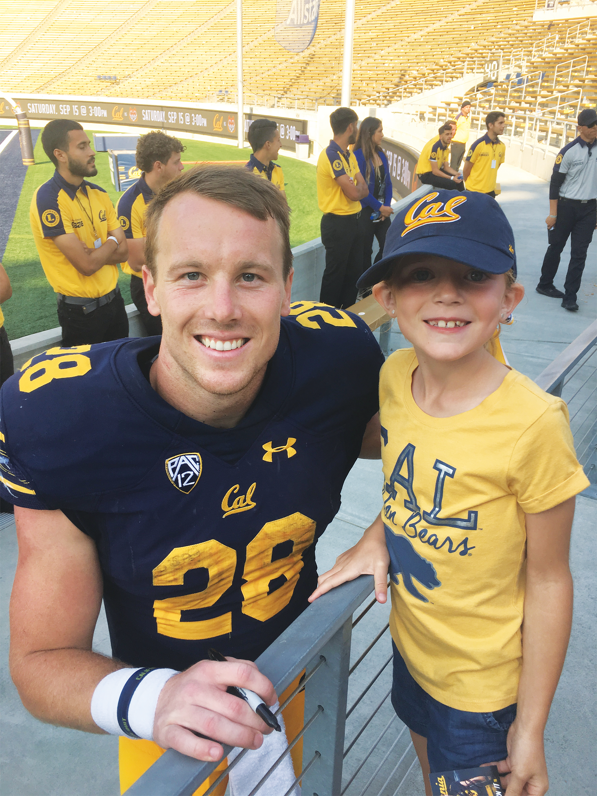 Photo of a grinning seven-year-old Andie Wiskerson in Cal gear meeting football star Patrick Laird '18.