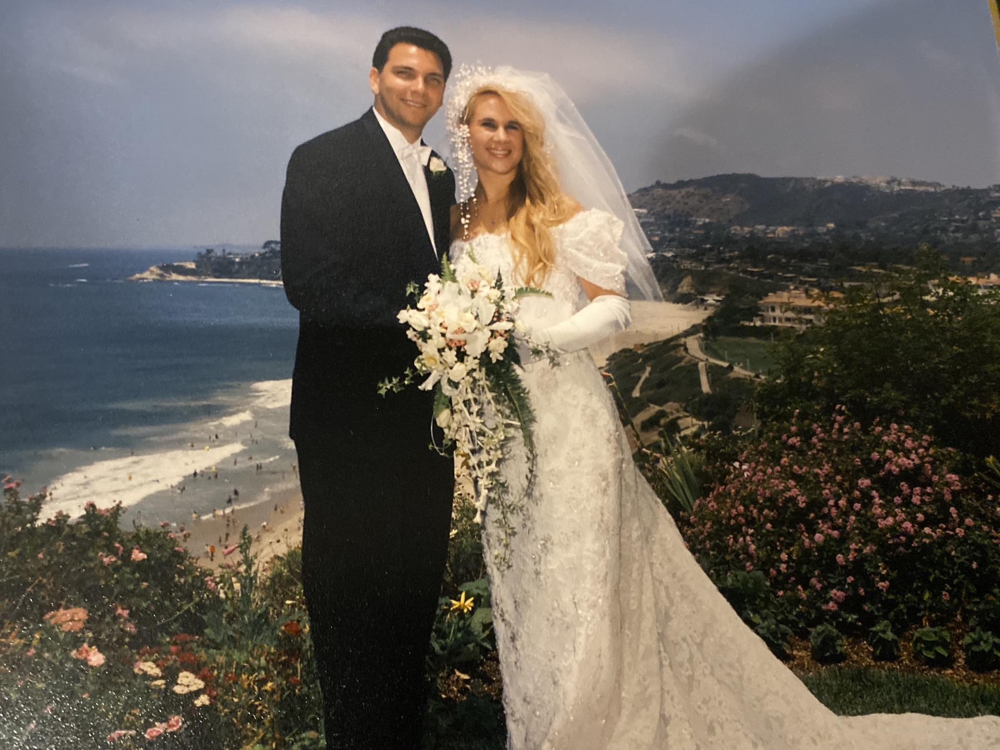 Photo of the newlyweds on a cliff overlooking the ocean