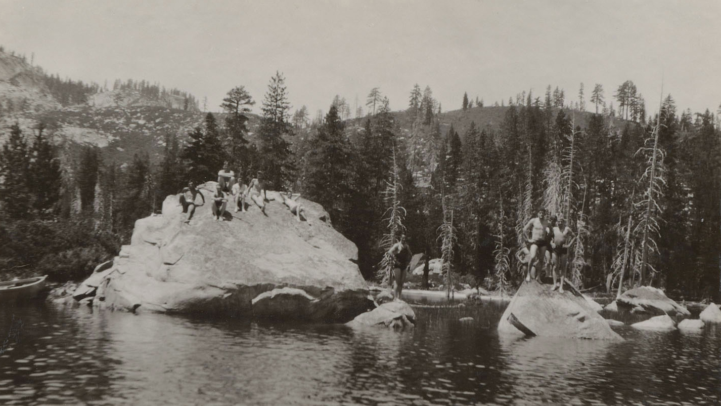Black-and-white photo of eight people in swimsuits standing on two large rocks in a lake in front of tall trees with mountains in the distance