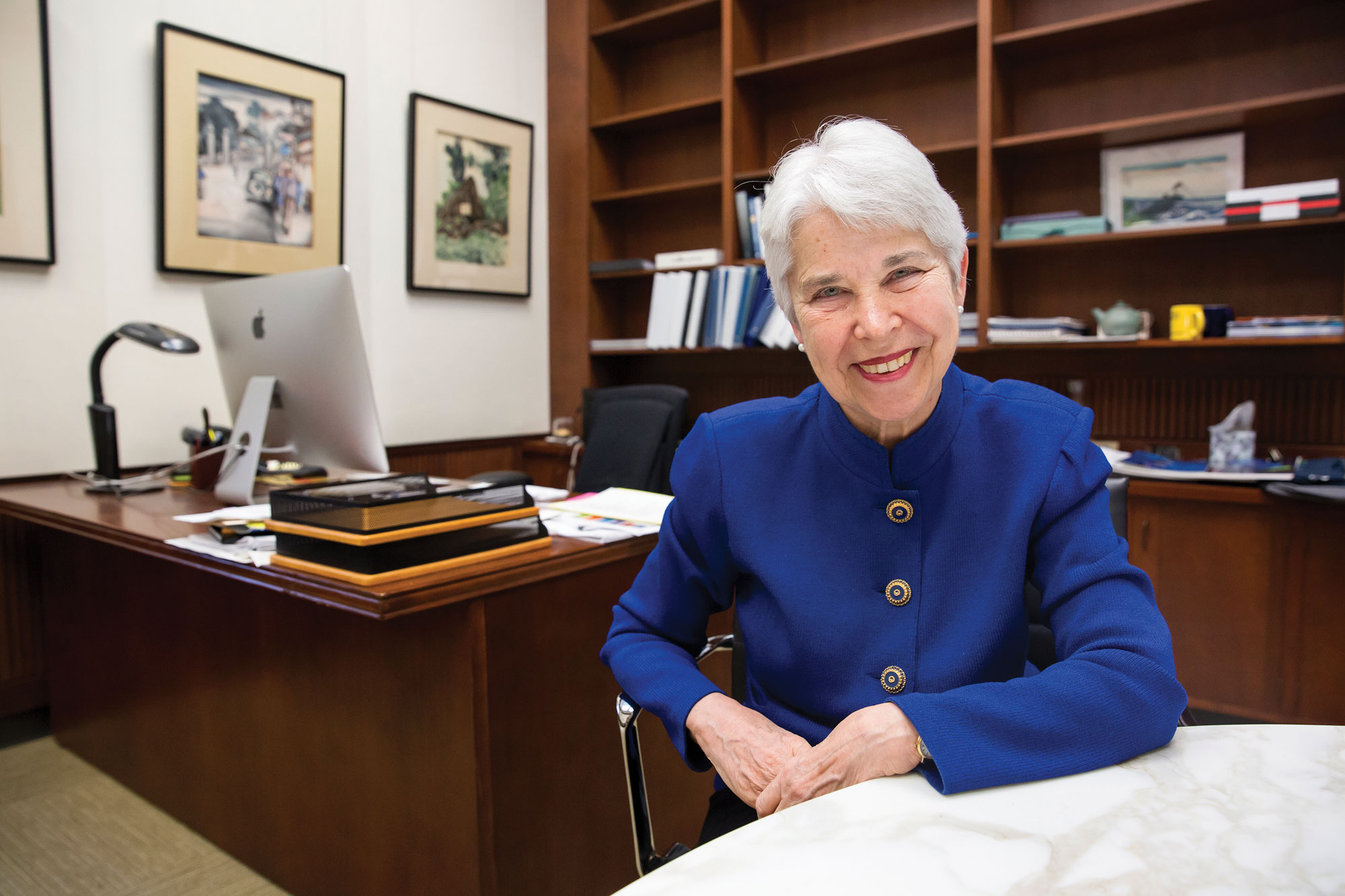 Photo of Chancellor Christ smiling at camera, sitting at her desk