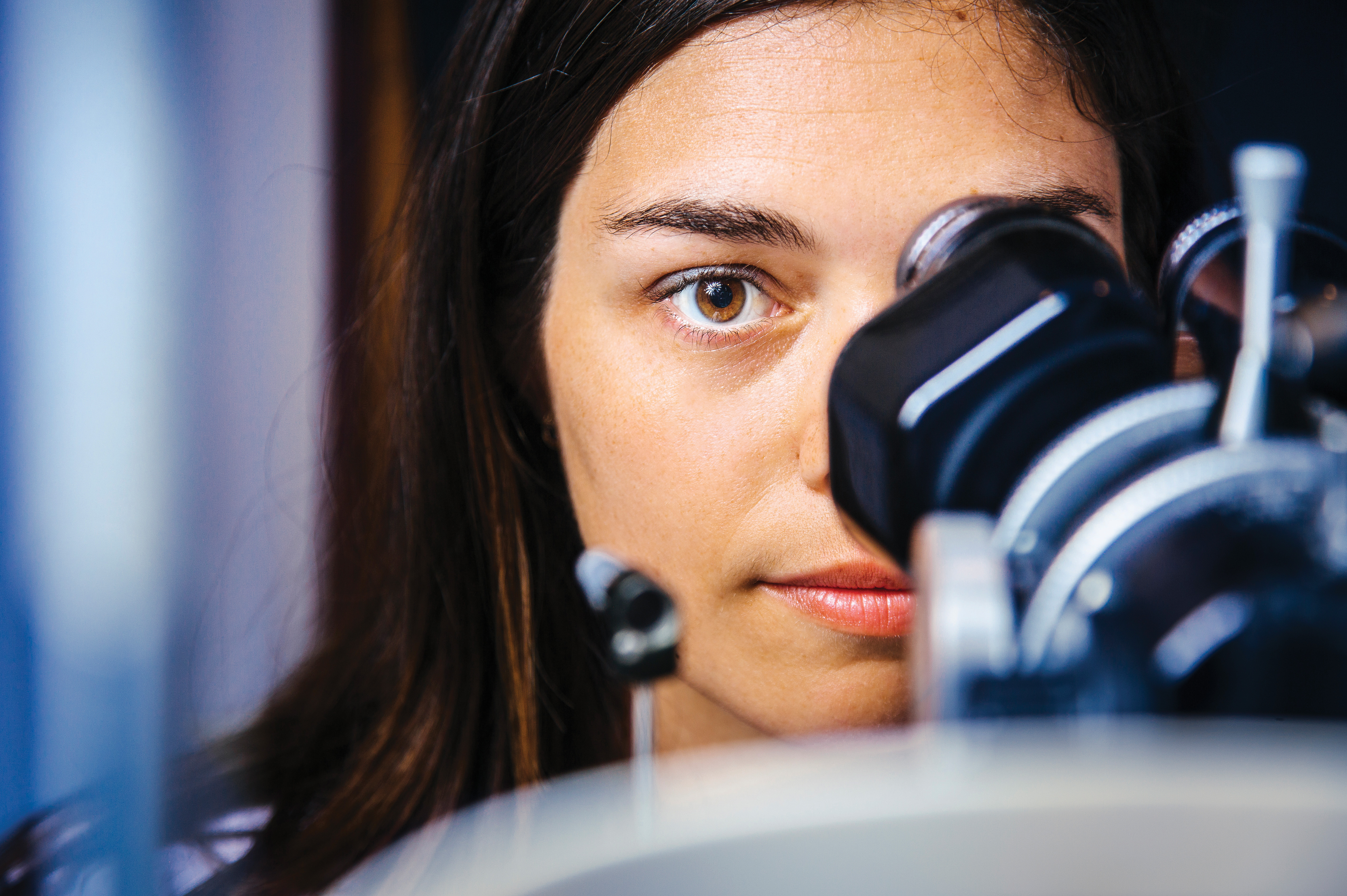 Photo of a young woman looking through the viewer on a piece of optometry equipment.