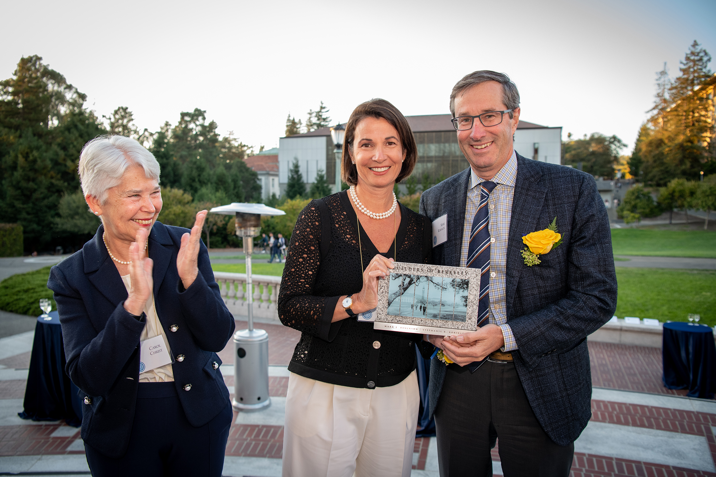Photo of Chancellor Christ clapping and looking warmly upon Stephanie and Mark, who are holding a plaque.