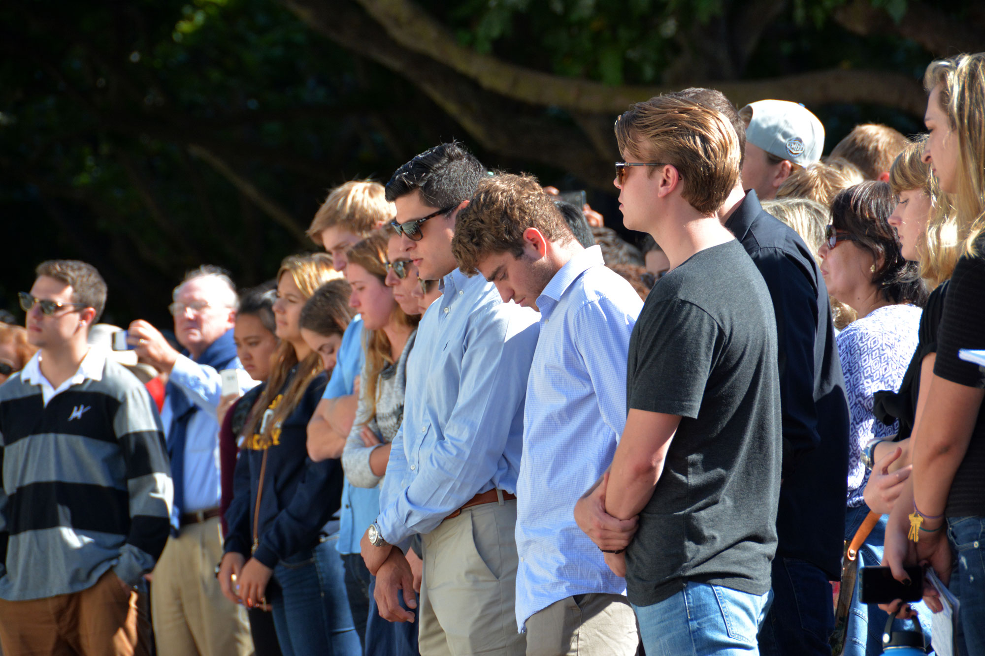 Photo of members of the Cal community at a memorial service, many with their heads bowed down.