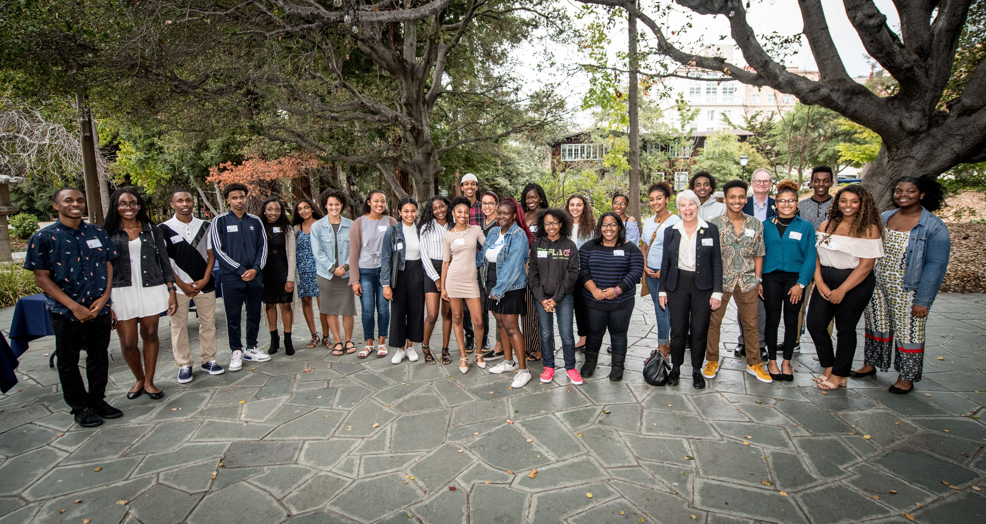 Photo of nearly 30 proud scholarship recipients on a stone walkway with the chancellor and other leaders.