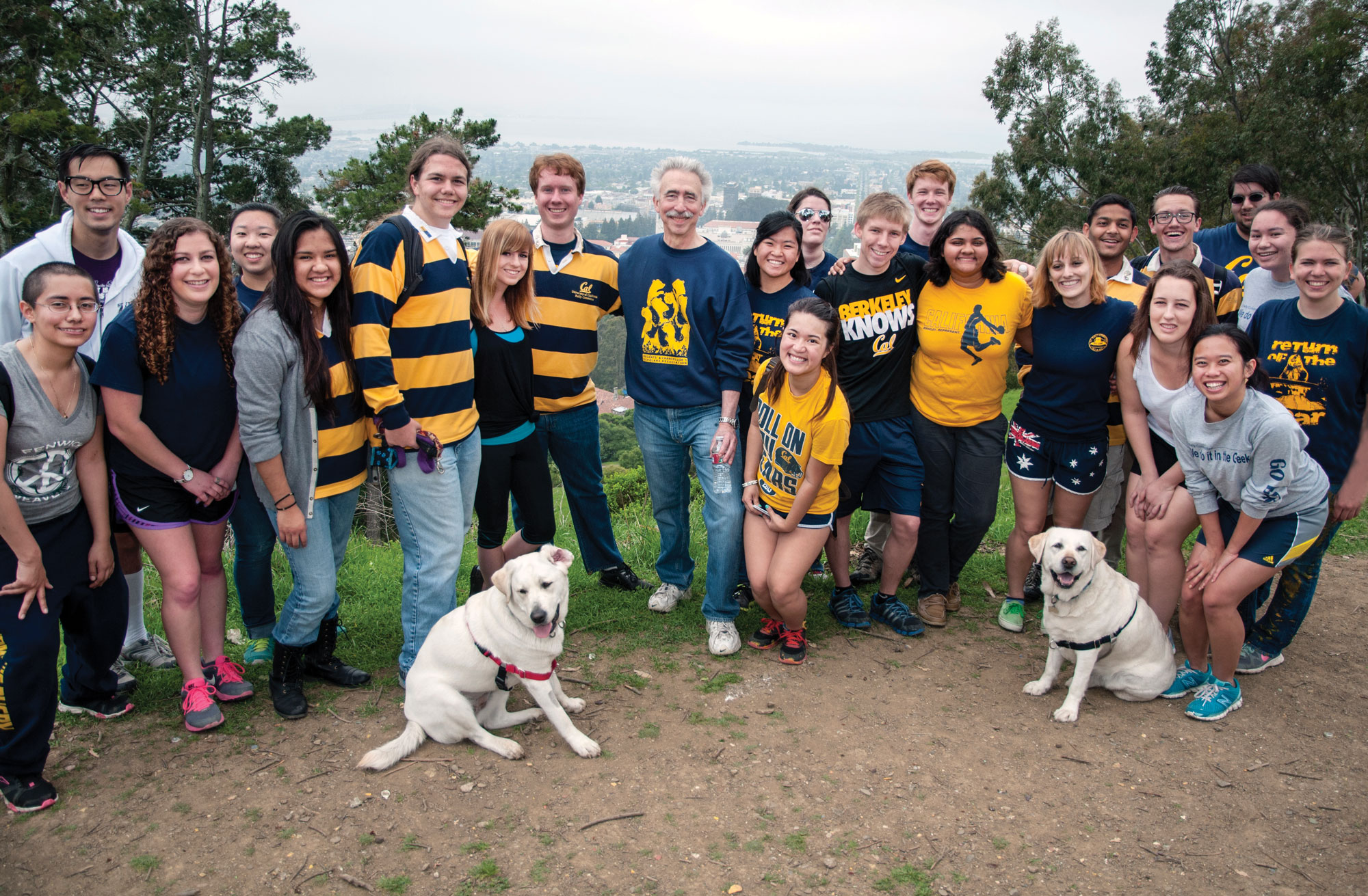 Photo of the chancellor and about 15 students, most wearing blue and gold attire, with a foggy city in the backgound.