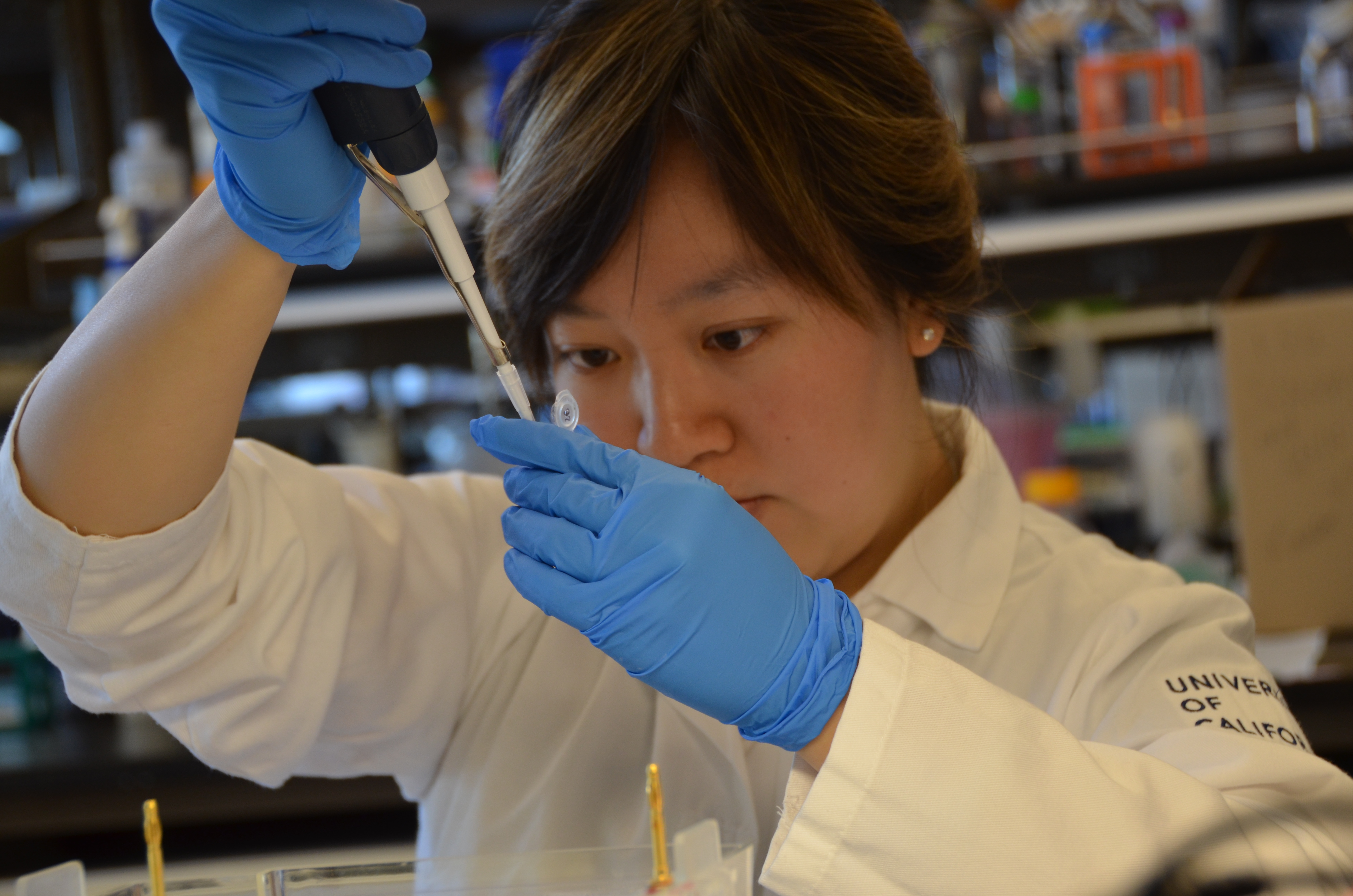 Photo of Jessica wearing a white lab coat and blue gloves using a pipette to transport a liquid.