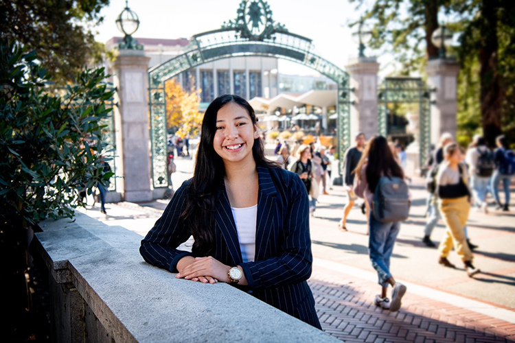 Photo of smiling young woman wearing a blue blazer, leaning one elbow on the low stone wall in front of Sather Gate