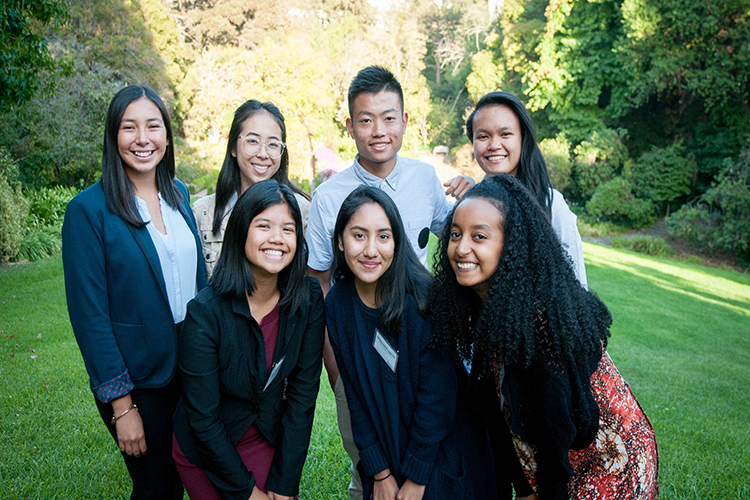 Photo of seven young people, standing in two rows with green grass and trees around them, smiling in to the camera