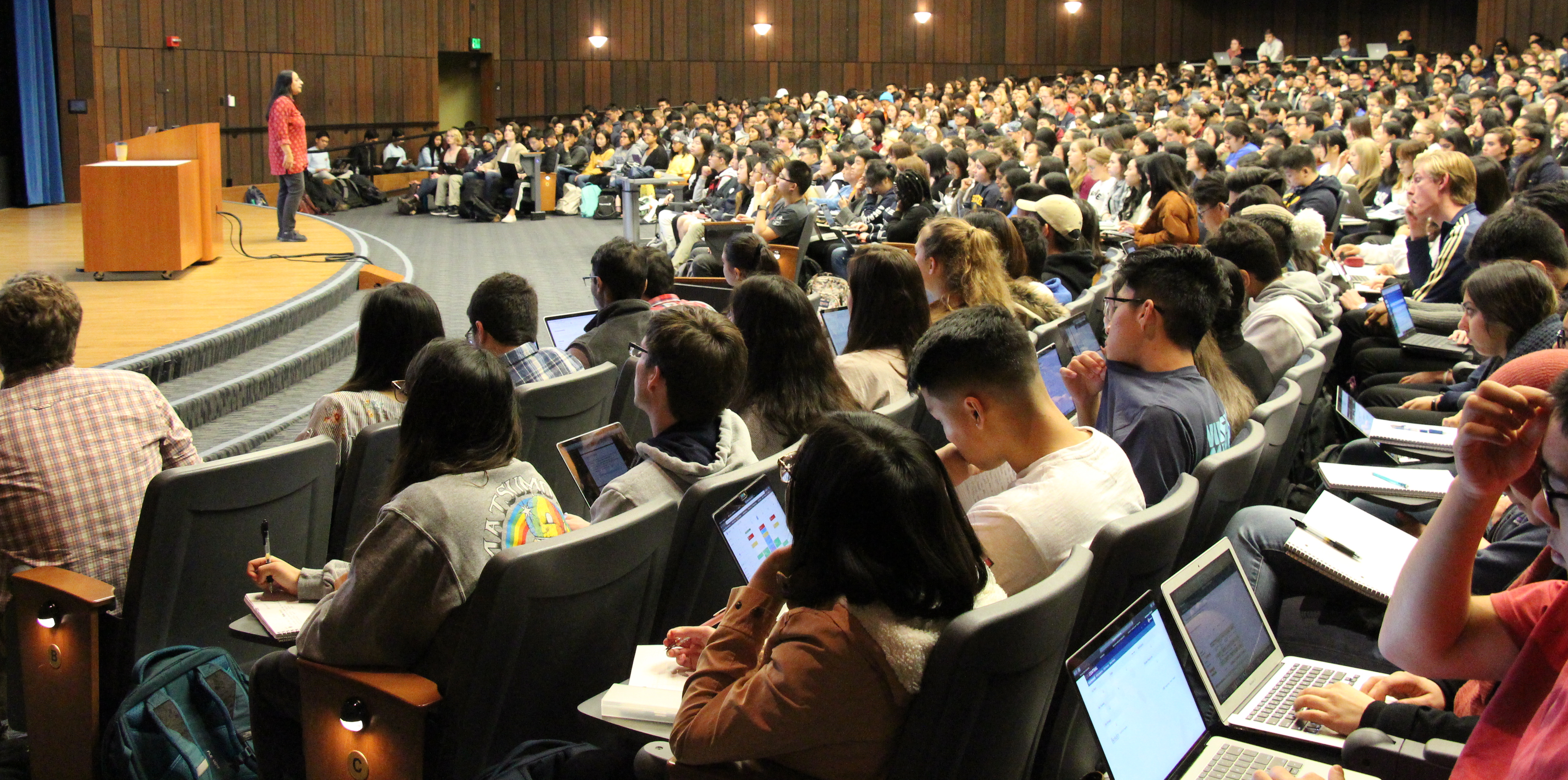 Photo of a full lecture hall, taken from the left side of the back