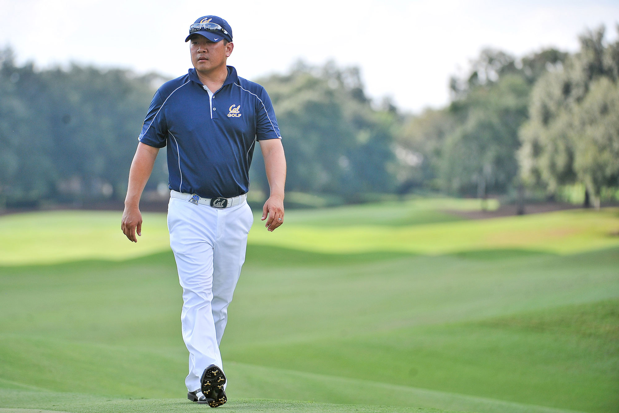 Photo of Chun in a Cal shirt walking on a golf course.
