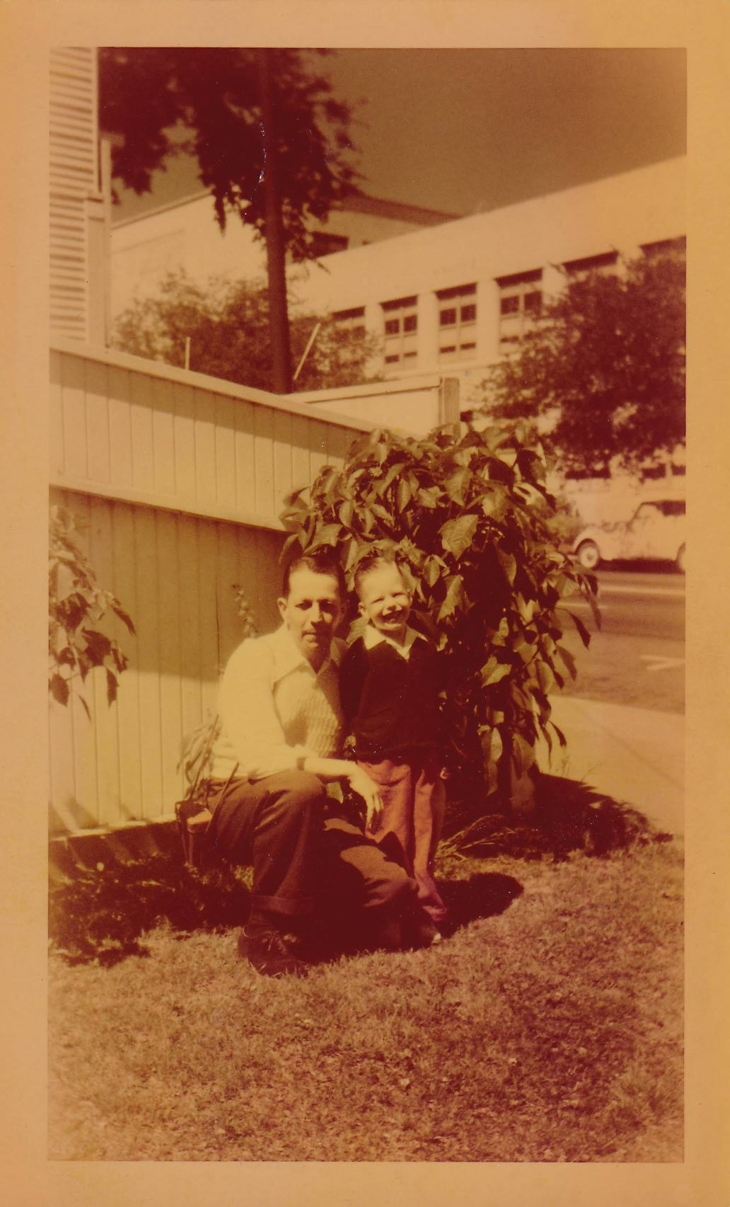 Sepia-toned photo of Greg as a toddler standing next to a man