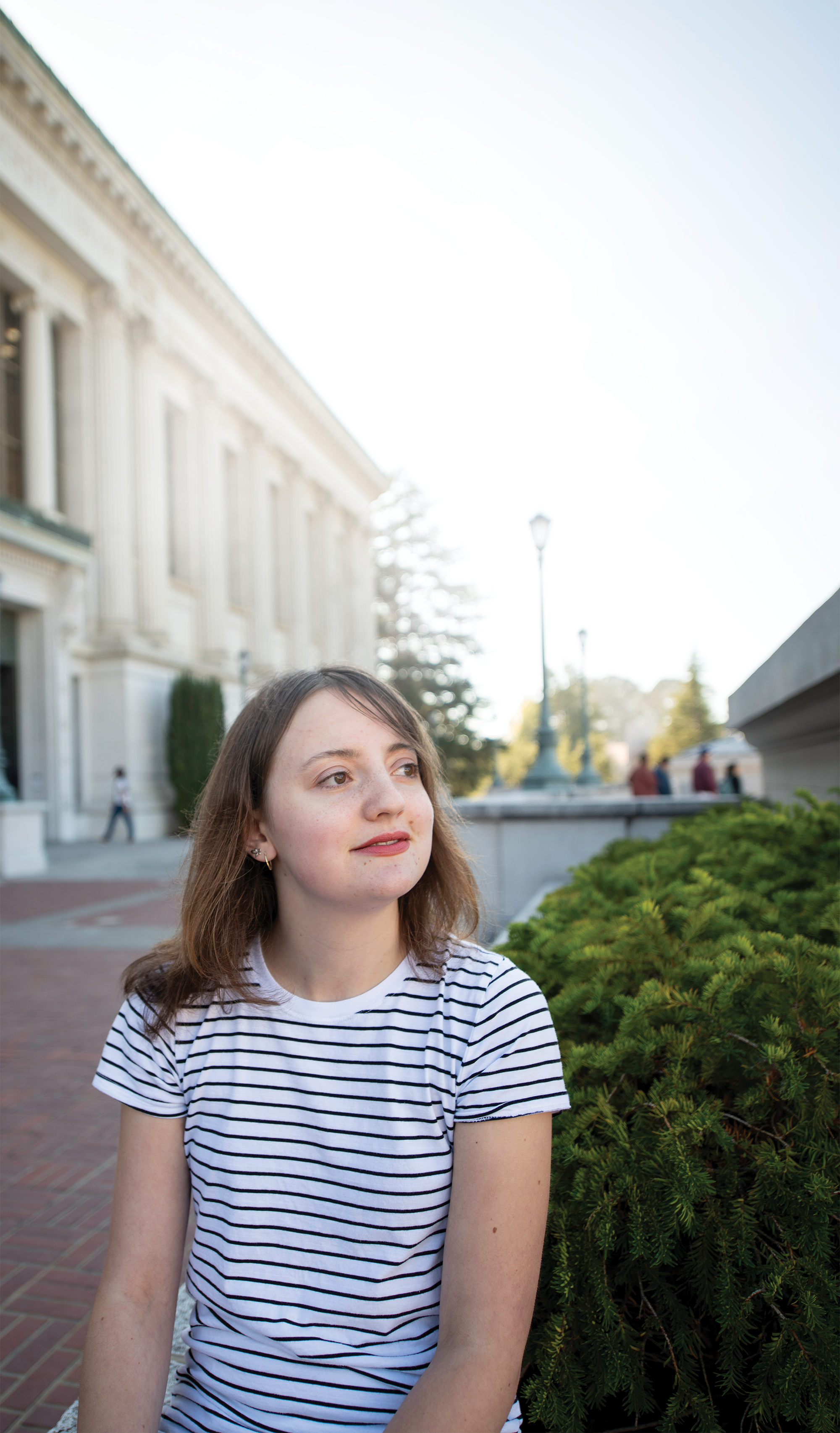Photo of Harriet Steele '19 on the plaza of Doe Library smiling and looking into the distance.