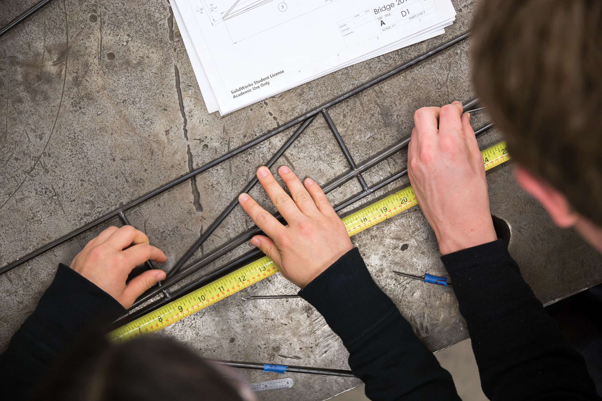 Aerial photo overlooking two students' hands with a ruler and other tools