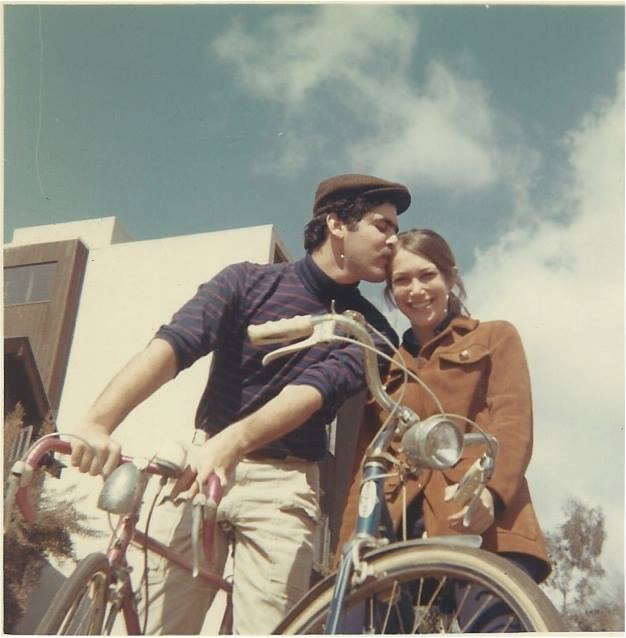 Jim, who's wearing a newsboy cap and striped shirt, leans in to kiss his new bride Gail, who's smiling at the camera. They're both on bikes.