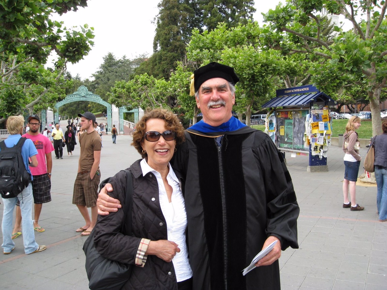 Jim, who is wearing his graduation cap and gown, hugs Gail. Sather Gate is in the background.