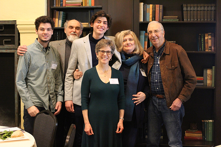 Photo of six people of varying ages, standing closely together, smiling into the camera, with books on shelves behind them