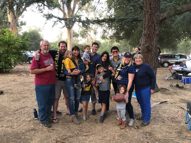 Photo of 13 members of the family, including a few cubs, huddled together in blue and gold clothes and one rogue Stanford tshirt.