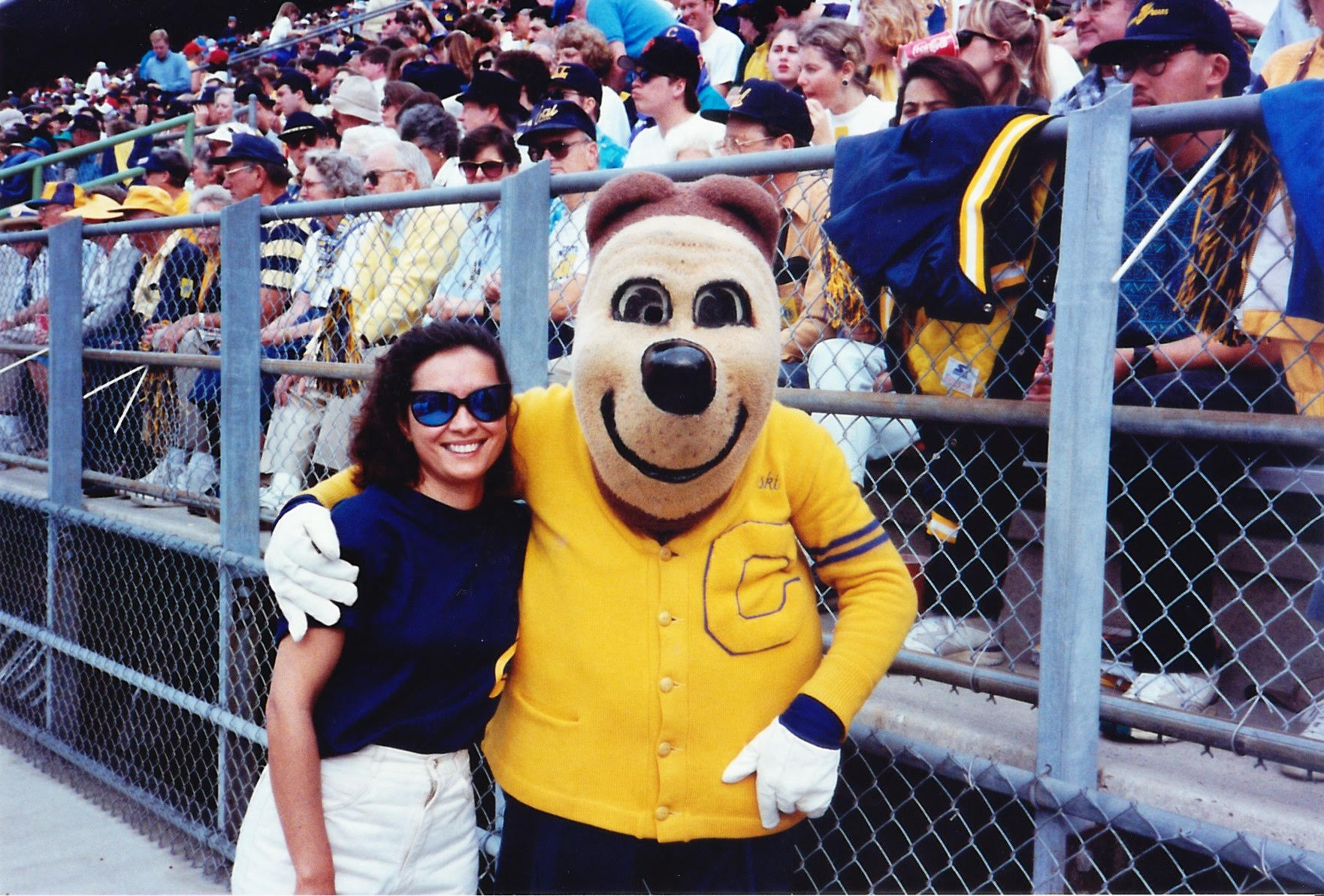 Photo of Michele and Oski in front of the stands. He's wearing his famous letter sweater and white gloves. She's wearing white shorts and a dark, sleeveless top.