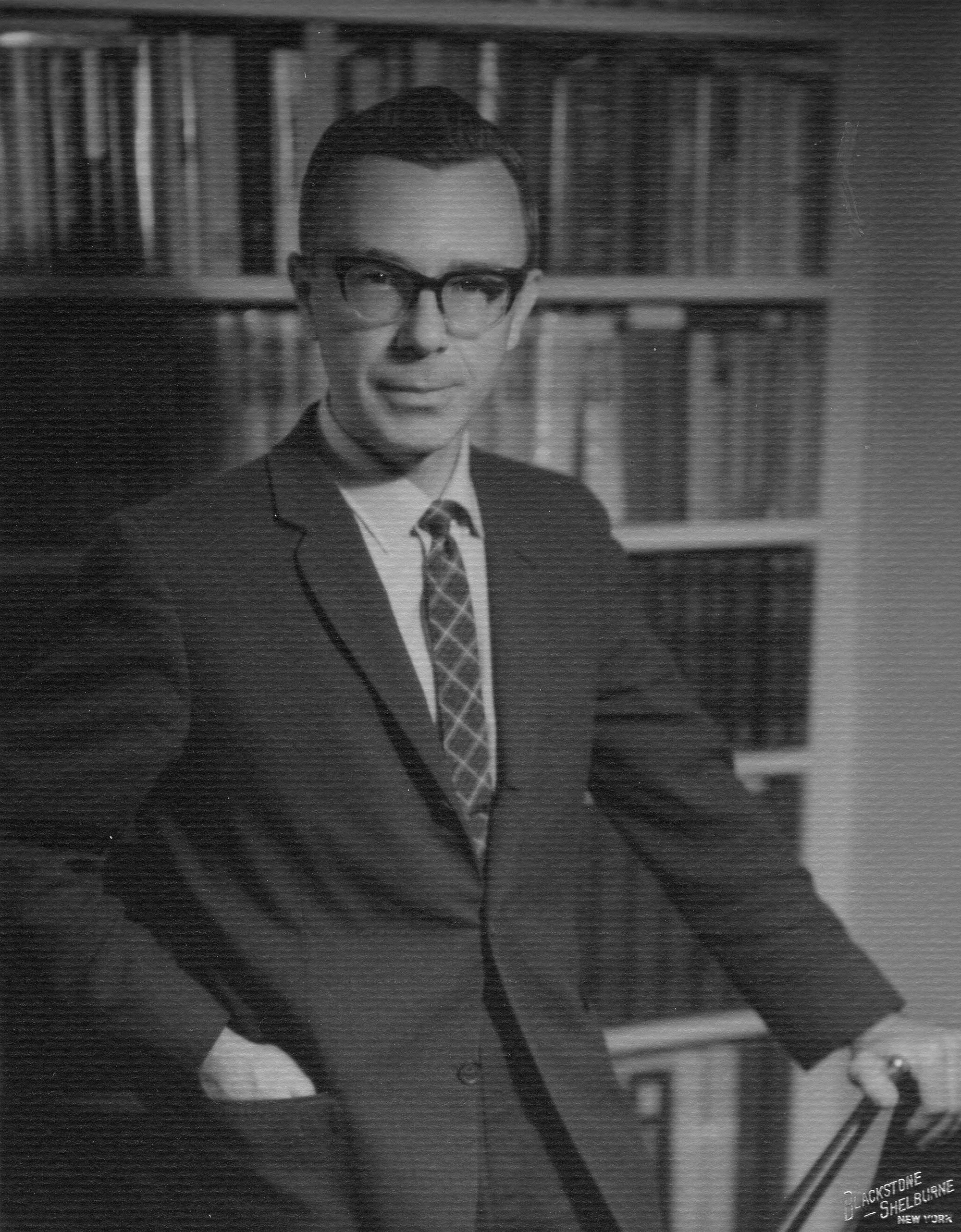 Photo of Robert circa mid-1960s in a coat and tie standing by a bookshelf
