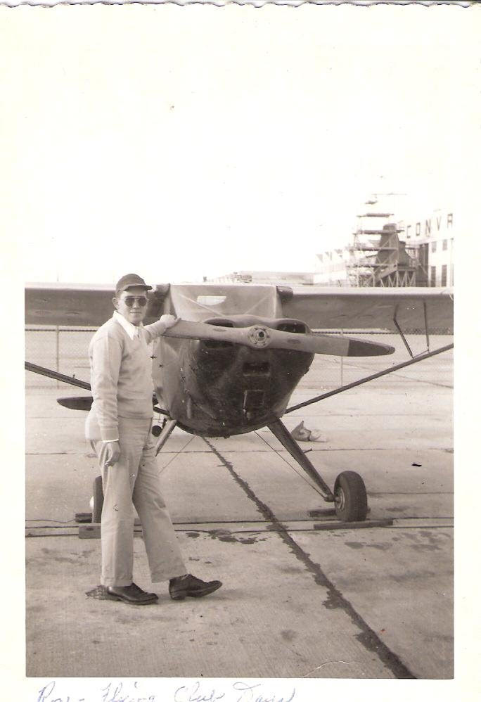 Black and white photo of Ron in a baseball cap and dark sunglasses standing next to a small plane.