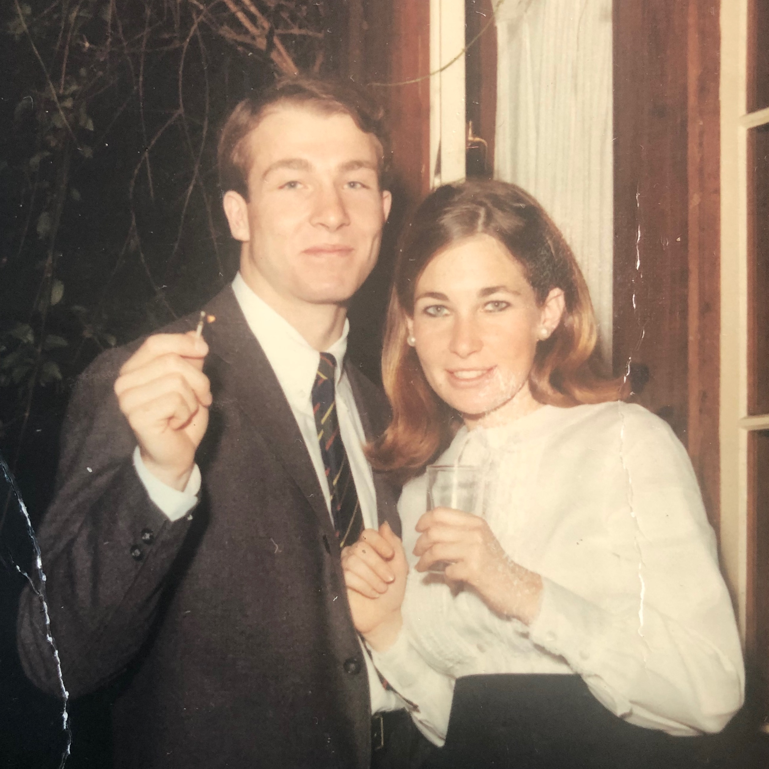Photo of John in a coat and tie and Vandy in a white top. He has his arm around her and they are smiling.