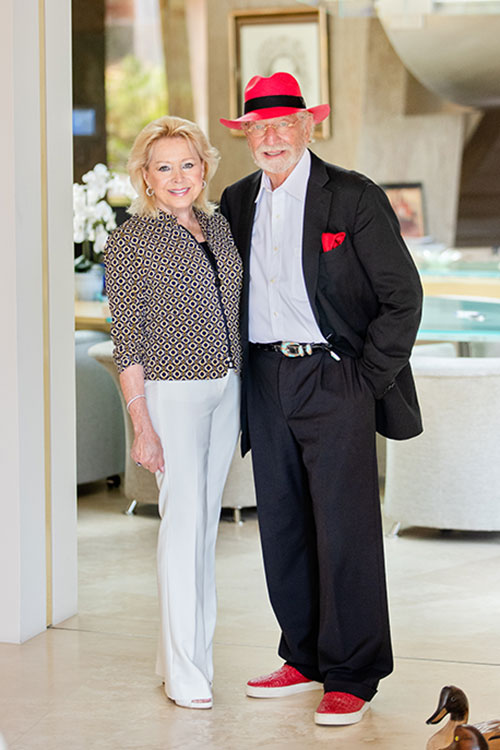 Photo of Nicole, wearing white pants and a diamond-patterned jacket, and Herbert, in his trademark red fedora.