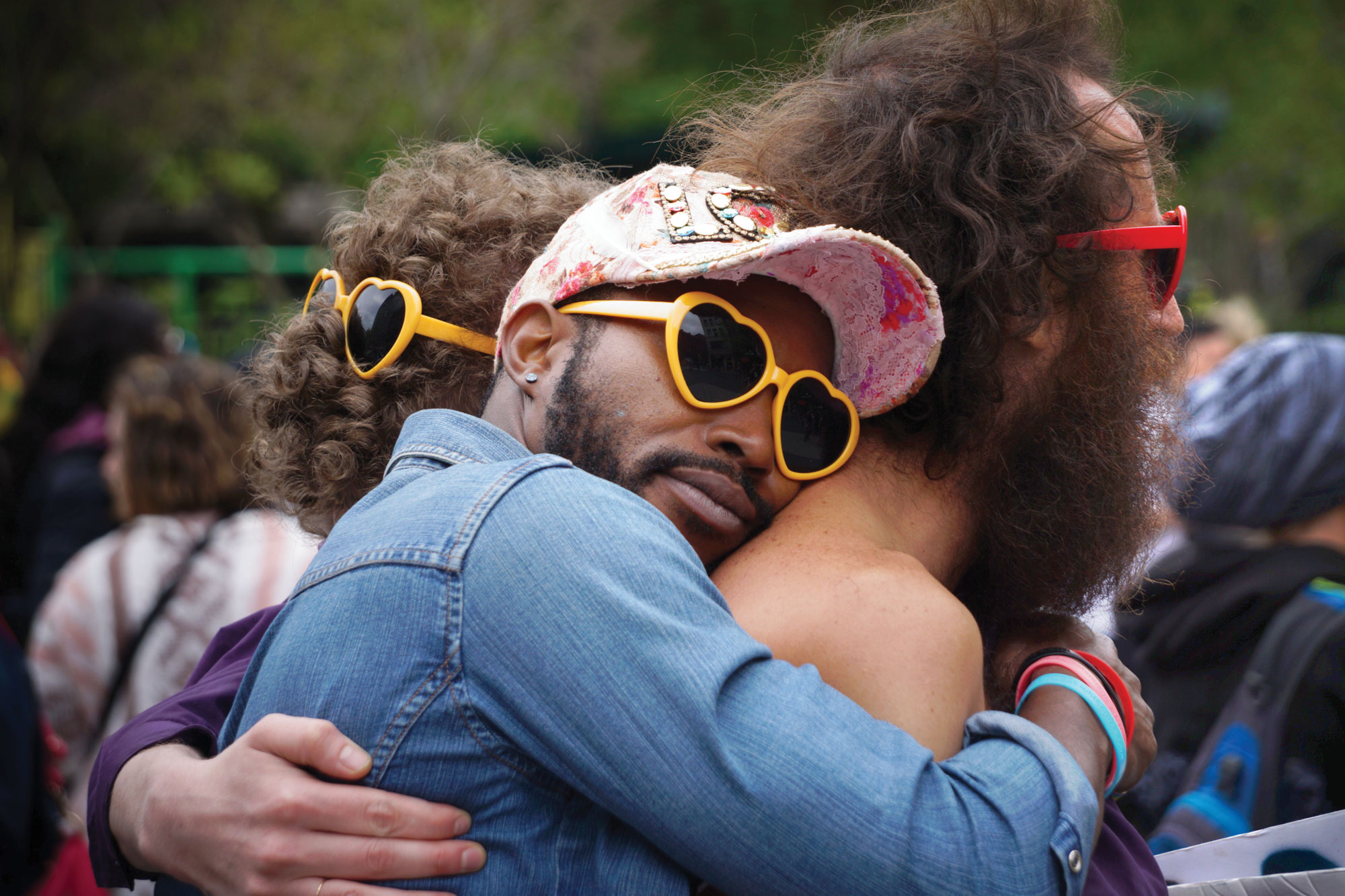Photo of man wearing heart-shaped sunglasses hugging another man.