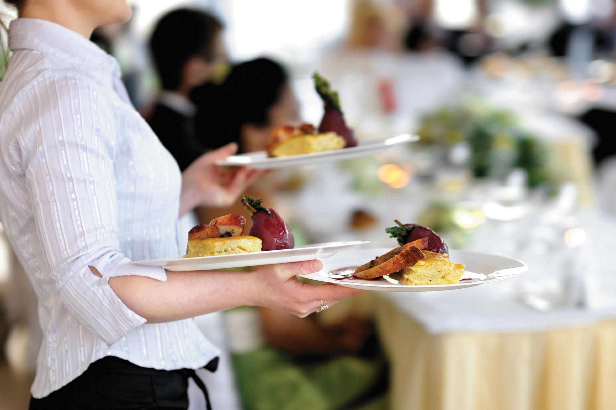 Photo of a waiter in a white shirt carrying three plates of food.