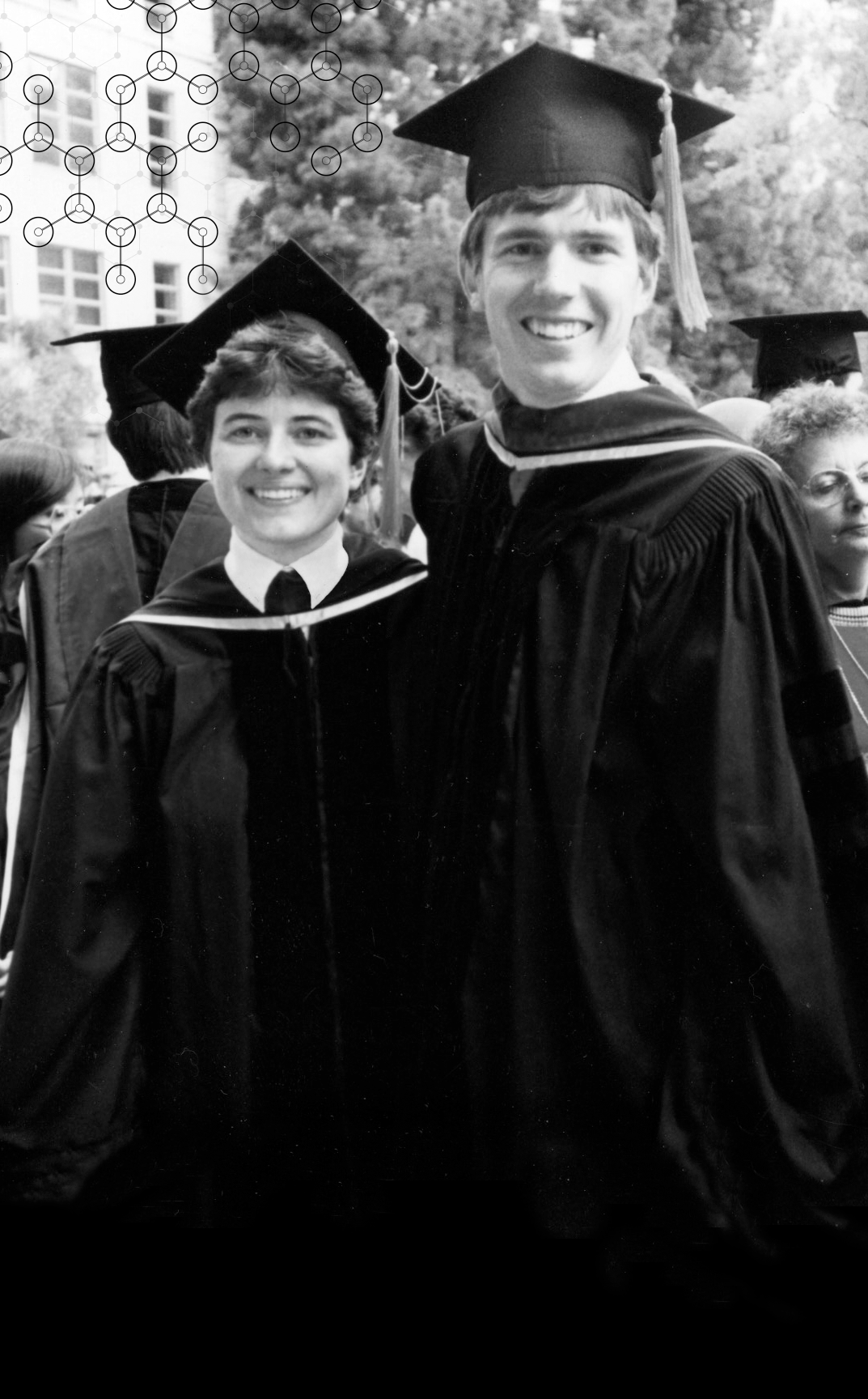Photo of Ann and Joe wearing their graduation robes and caps.