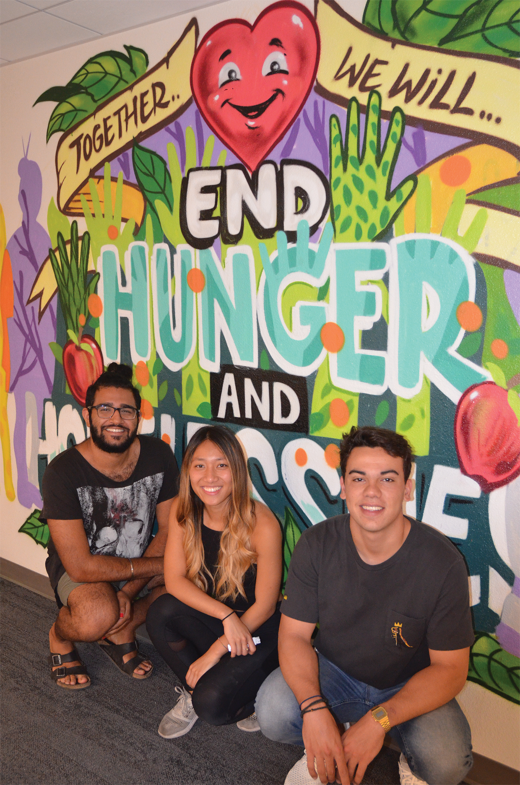 "Photo of the staff and student leaders kneeling in front of a brightly painted mural that says, ""Together we will end hunger and homelessness."""