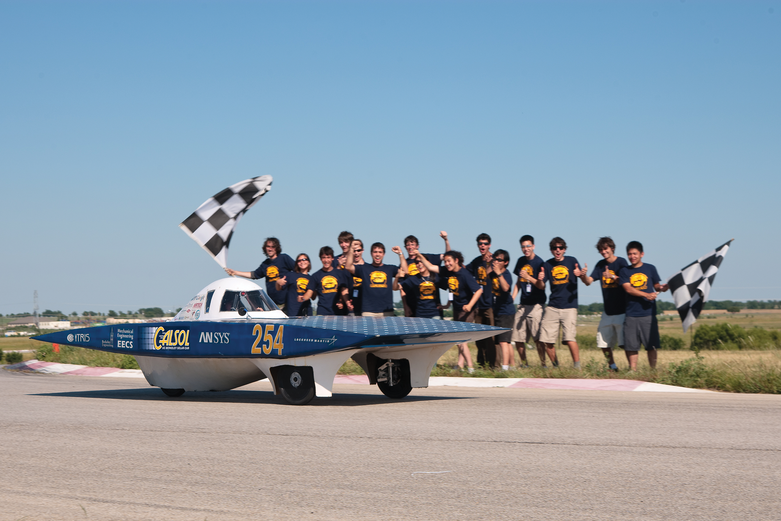 The group is cheering in front of one of its car inventions.