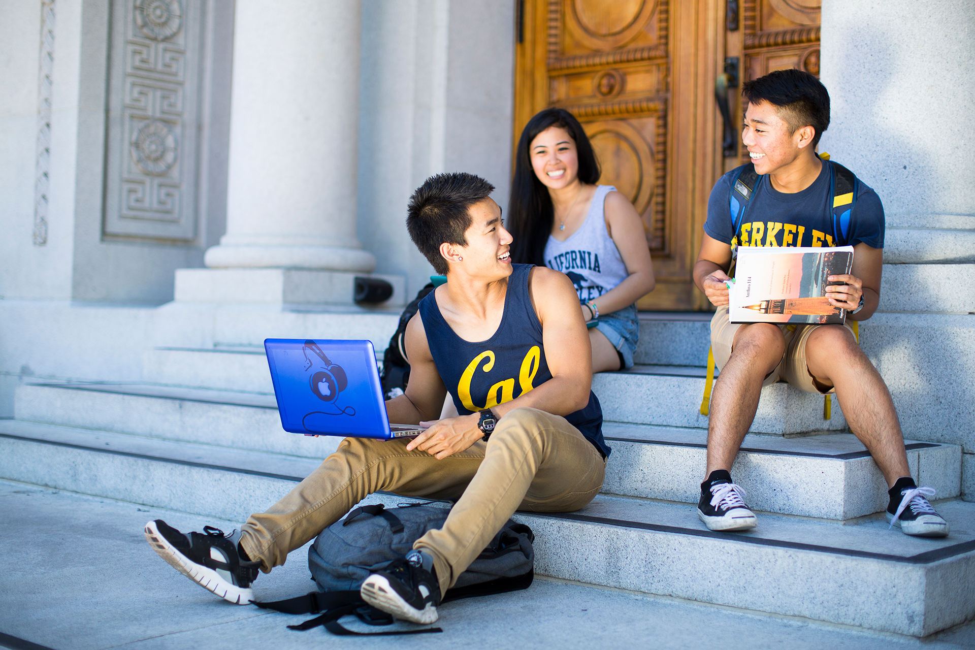 Photo of three smiling students sitting on the steps.